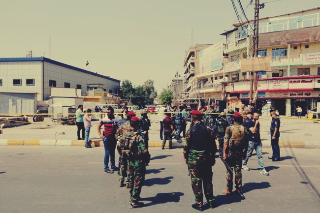 Iraqi security forces gather at the site of a suicide bomb blast in Baghdad al-Jadida