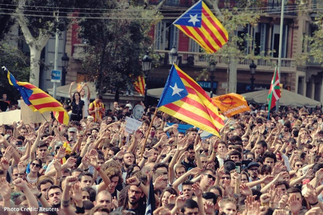 People shout as Esteladas (Catalan separatist flags) flutter during a protest the day after the banned independence referendum in Barcelona
